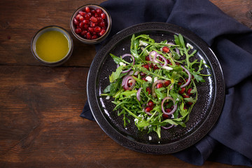 Arugula or rocket salad with pomegranate, red onions and parmesan served on a dark plate, small bowls with seeds and dressing, rustic wooden background, copy space, high angle view from above