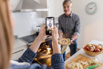 Woman photographing man with freshly baked apple pie