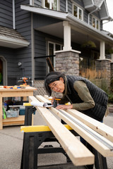 Woman measuring wood for home improvement work
