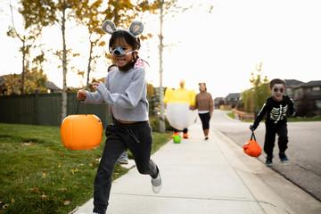 Children racing on street with Halloween pumpkin buckets, parents in background