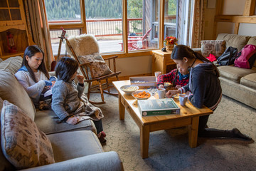 Family relaxing and playing game in cabin living room Fototapete
