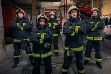 Group of firefighters standing confident with arms crossed. Firemen ready for emergency service.