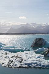 Icebergs and view of Jokulsárlón glacier lagoon in south Iceland, tourist popular natural attraction. Sunny summer day.