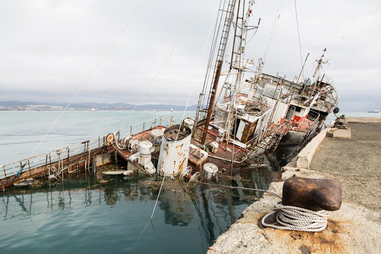 An old fishing boat sunk at a pier in seaport