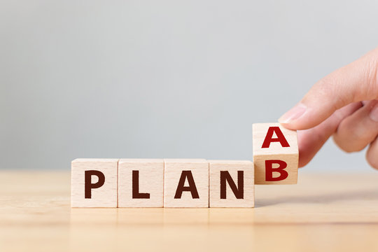 Hand flip over wooden cube block word plan A to plan B