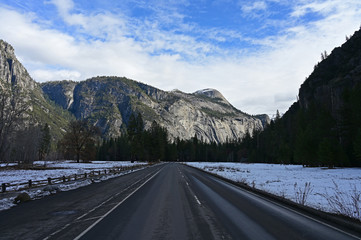 Road in Yosemite Valley in Yosemite National Park, California with granite rock formations in background under winter cloudscape.