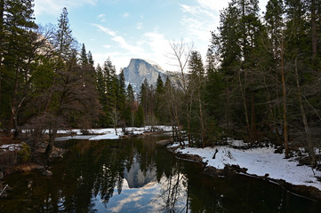 Half Dome and surrounding woods reflected in Merced River in Yosemite National Park, California under winter cloudscape.