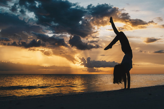 A woman doing a graceful handstand on the beach in silhouette