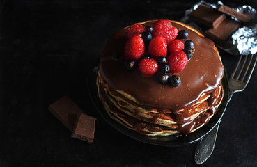 Homemade pancakes with chocolate and fresh berries on a dark background. Image with horizontal orientation.