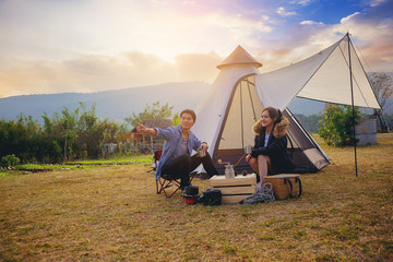 Photo sur Aluminium Camping Young couples have good time morning on camping trip with sunrise background. Couples enjoy camping with morning coffee.
