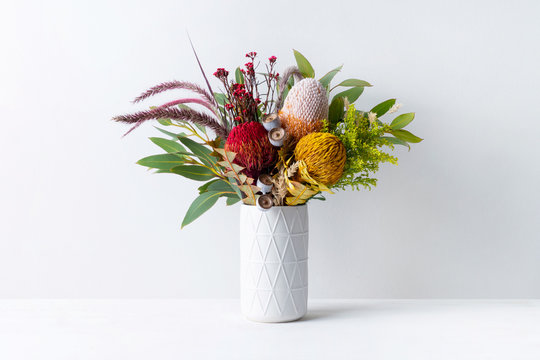 Beautiful floral arrangement of mostly Australian native banksias, eucalyptus leaves and gum nuts, fountain grass and dried kangaroo grass, in a white vase on a white table with a white background.
