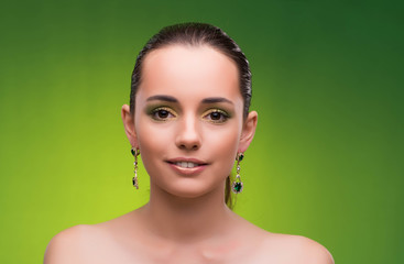 Wall Mural - Young woman in beauty concept on green background