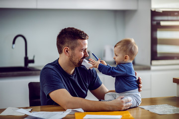 Young proud dad sitting at dining table, having bill in mouth and holding his son. Toddler is sitting on table and helping his dad to fill in bill.