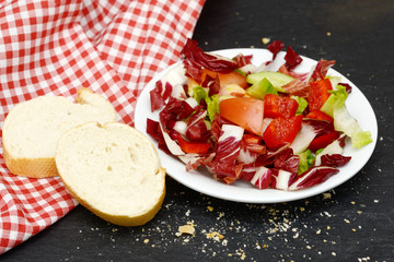 mixed salad and rustic crusty white bread lying on black slate in the kitchen