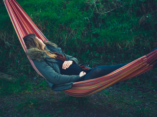 Pregnant woman relaxing in hammock on a winter day