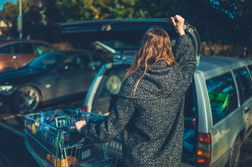 Woman loading her shopping into her station wagon car