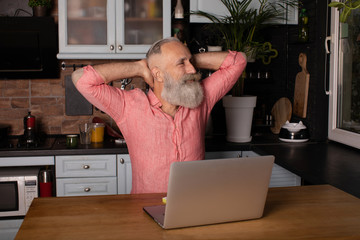 Smiling Bearded senior man Stretching Hands Sitting At Laptop Working At Home.