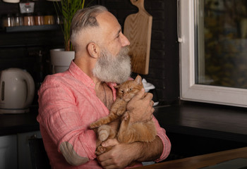Bearded senior man holding cute cat at home.