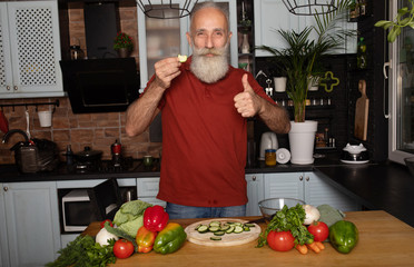 Picture of mature handsome bearded man standing at the kitchen and cooking salad