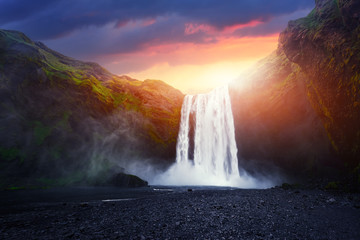 Fotobehang Watervallen Incredible landscape with Skogafoss waterfall and unreal sunset sky. Iceland, Europe