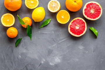 Citrus fruits frame - halfs of lemons, grapefruits, leaves - on grey background top-down copy space