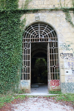 2019.06.16 - Limbiate, Milan, Italy, photographic reportage madhouse in Mombello, abandoned psychiatric hospital entrance of the structure in wrought iron with broken glass