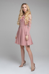 Full length stock photo of gorgeous blonde woman with long wavy hair wearing romantic pink dress with print on chest. Model is holding the skirt. Wearing high beige heels. Isolate.