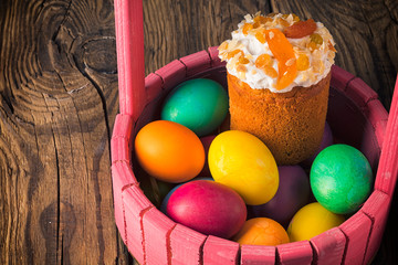 Easter cake and painted eggs on wooden table
