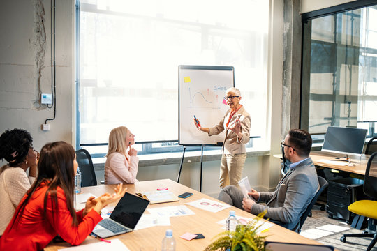 Aged attractive businesswoman giving presentation at corporate diverse group meeting, senior female business coach, woman boss or team leader presenting new strategic plan to multiracial employees