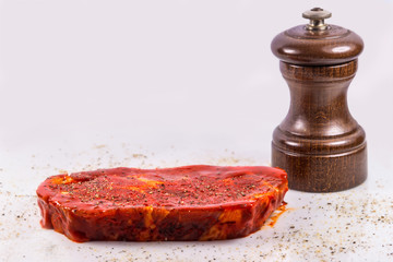 raw marinated pork neck with pepper mill