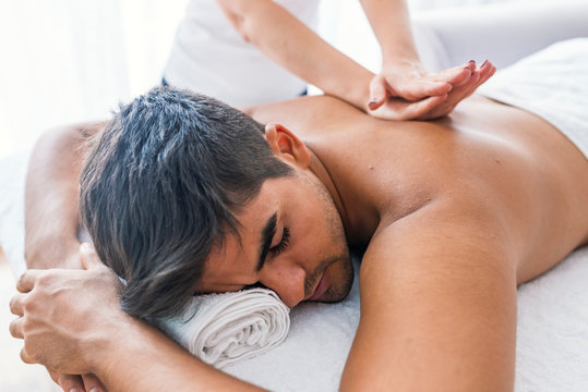 Portrait Of Man Receiving Massage Treatment From Female Hand. Close-up of masseur's hands and a client's back. Man getting relaxing massage in spa. Man receiving back massage from masseur