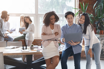 Diverse group of colleagues having conversation in office