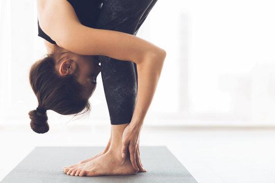 Woman stretching standing in modern light studio