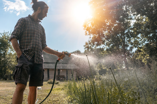 Hipster young man watering plants a country house, summer spring and garden care, organic products, eco-friendly lifestyle
