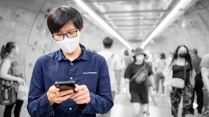Asian man wearing surgical face mask using smartphone in subway tunnel with crowded people walking pass. Wuhan coronavirus outbreak prevention in public area. Health care and medical concept