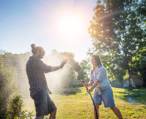 young happy beautiful couple hosing in the garden, summer happiness and love concept, poured water...