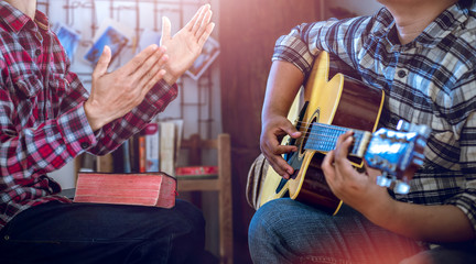 Two young christian sing a song and worship God, focus at hand playing a guitar, Christian worship concept.