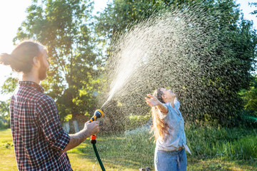 young happy beautiful couple hosing in the garden, summer happiness and love concept, poured water from a garden hose of a spray