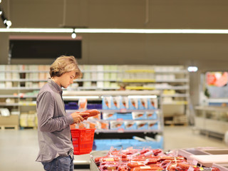 man choosing a dairy products at supermarket