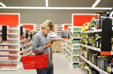 Young man shopping in supermarket, reading product information