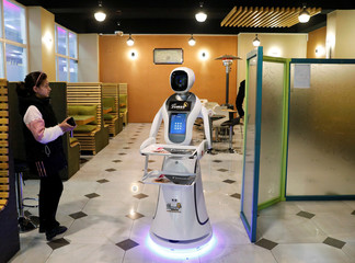A girl stands next to a waitress robot (Timea) at the Times Fast Food restaurant in Kabul