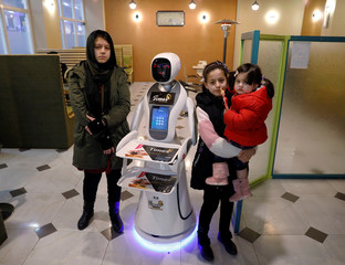 Afghan girls pose for a photo with a waitress robot (Timea) at the Times Fast Food restaurant in Kabul