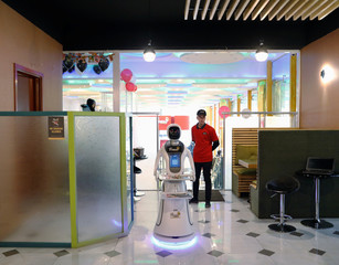 A waitress robot (Timea) brings food to a table at the Times Fast Food restaurant in Kabul
