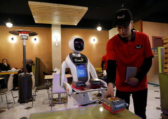 A waitress robot (Timea) delivers food to a table at the Times Fast Food restaurant in Kabul
