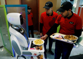 A waiter places plates with food onto the tray of a waitress robot (Timea) at the Times Fast Food restaurant in Kabul