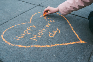 little girl painting the heart of Mother's Day with orange chalk on the floor seen up close