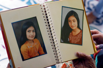 A family member holds an album with photographs of Maham Ali Khan at the family's residence in Karachi