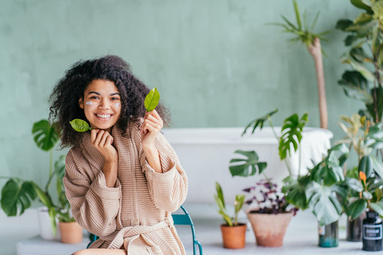 Beauty portrait of playful woman in bathroom covering her eyes with lemon tree leaves in hand with green plants on background. Skincare, cleansing, eco, organic, zero waste, reduce, reuse, recycle.