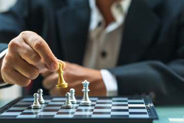 Business man holding The king chess for finishing the game
