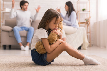 Upset Little Girl Cuddling Teddy Bear, Suffering From Parents Arguing